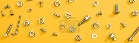 Photo for Top view of metal nuts and bolts on yellow background, panoramic shot - Royalty Free Image