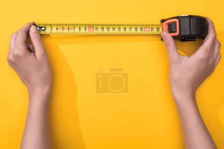 Top view of man holding industrial measuring tape on yellow background