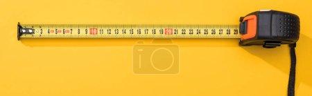 Photo pour Vue de dessus du ruban à mesurer industriel sur fond jaune, vue panoramique - image libre de droit