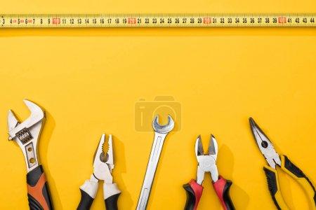 Photo pour Vue en haut du ruban à mesurer industriel près des clés et des pinces sur fond jaune - image libre de droit