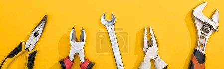 Photo for Top view of wrenches and pliers on yellow background, panoramic shot - Royalty Free Image