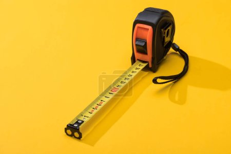 Industrial measuring tape with shadow on yellow background