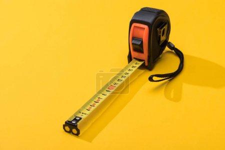 Photo pour Ruban à mesurer industriel avec ombre sur fond jaune - image libre de droit