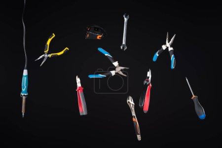 Photo pour Ensemble d'outils lévitants dans l'air isolés sur noir - image libre de droit