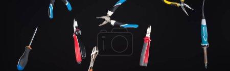 Photo pour Clés, tournevis et pinces levant à l'air isolé sur une pellicule noire panoramique - image libre de droit
