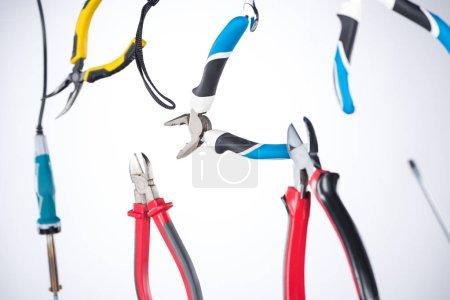 Photo pour Focus sélectif des pinces et des outils levant dans l'air isolé sur gris - image libre de droit