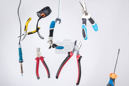 Photo for Set of tools with pliers and measuring tape levitating in air isolated on grey - Royalty Free Image