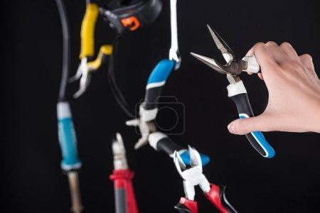 Photo pour Vue croustillante d'un homme tenant des pinces avec lévitation dans l'air outils isolés sur noir - image libre de droit