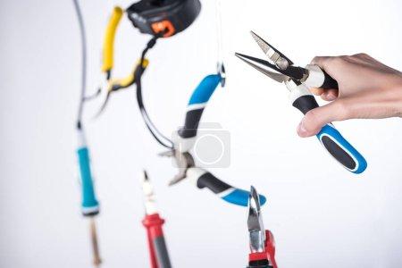 Photo pour Vue croustillante d'un homme tenant des pinces avec des outils lévitants dans l'air isolé sur gris - image libre de droit