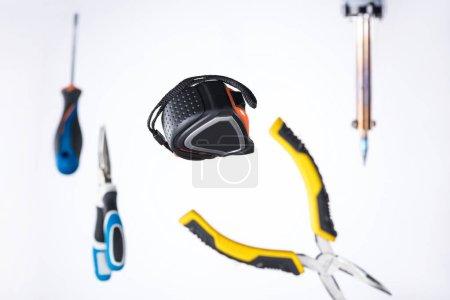 Photo pour Mise au point sélective d'un ruban à mesurer muni d'outils lévitant à l'air isolé sur blanc - image libre de droit