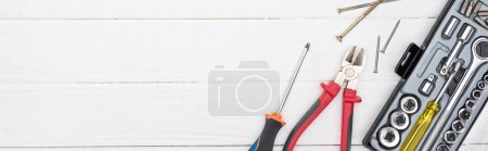 Photo for Top view of tool set with nails and wood screws on white wooden surface, panoramic shot - Royalty Free Image