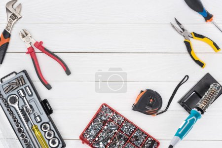Photo for Top view of tools with soldering iron and pliers on white wooden background - Royalty Free Image