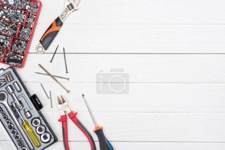 Foto de Vista superior de las cajas de herramientas con llaves, destornilladores y pinzas sobre fondo de madera blanca. - Imagen libre de derechos