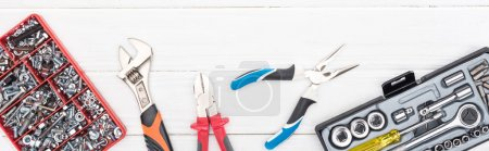 Foto de Vista superior de las cajas de herramientas con llaves y pinzas en la superficie de madera blanca, tiro panorámico. - Imagen libre de derechos