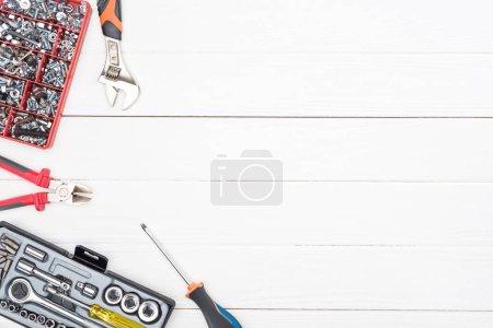 Foto de Vista superior de las cajas de herramientas con llaves y pinzas sobre fondo de madera blanca. - Imagen libre de derechos