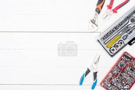 Foto de Vista superior de las cajas de herramientas con llaves, tornillos y pinzas de nueces sobre la superficie blanca de madera. - Imagen libre de derechos