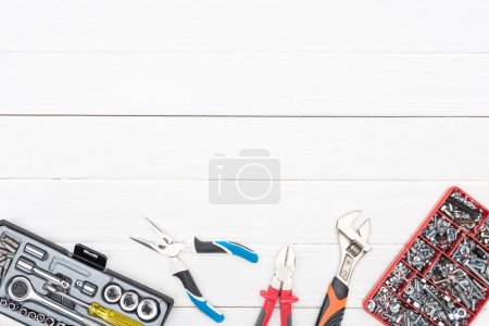 Photo for Top view of wrenches with tool boxes and pliers on white wooden background - Royalty Free Image