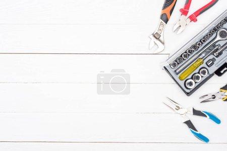 Photo pour Vue du dessus de la clé dans la boîte à outils et les pinces sur fond blanc en bois - image libre de droit