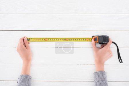 Photo pour Vue de dessus de l'homme tenant du ruban à mesurer industriel sur une surface en bois blanc - image libre de droit
