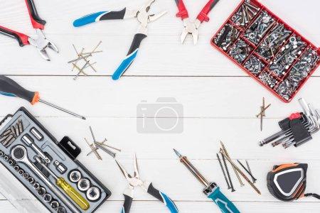Photo pour Cadre d'outils avec boîtes à outils sur une surface blanche en bois - image libre de droit