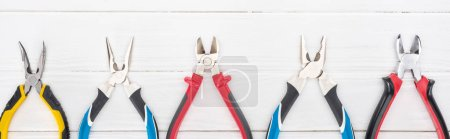 Photo for Top view of pliers on white wooden background, panoramic shot - Royalty Free Image
