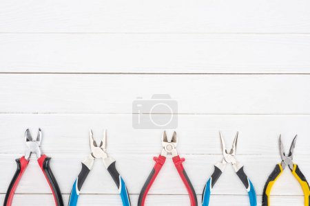 Photo for Top view of pliers on white wooden surface with copy space - Royalty Free Image