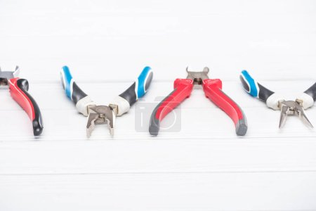 Photo for Line from pliers on white wooden surface - Royalty Free Image