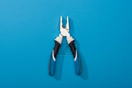 Top view of pliers on blue surface with copy space