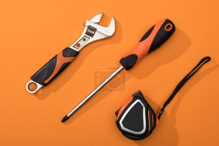 Photo for Top view of wrench, screwdriver and measuring tape on orange background - Royalty Free Image