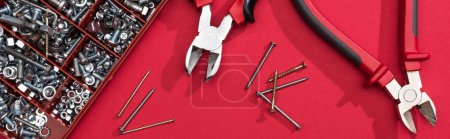 Photo for Top view of tool box with pliers and nails on red background, panoramic shot - Royalty Free Image