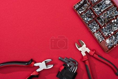 Photo pour Vue du dessus de la boîte à outils avec pinces et clés hexagonales sur la surface rouge - image libre de droit