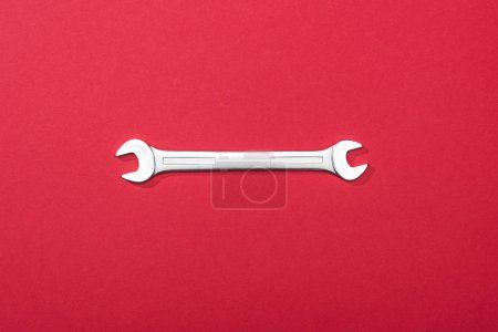 Photo for Top view of metal wrench on red background - Royalty Free Image
