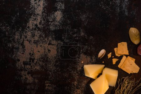 Photo for Top view of cheese platter with pistachios, olives and crackers on weathered surface - Royalty Free Image
