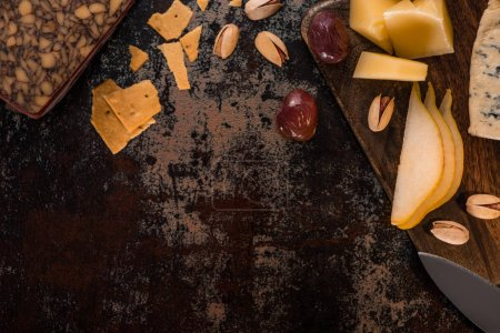 Photo for Top view of cheese platter with pistachios, sliced pear, olives and crackers on weathered surface - Royalty Free Image