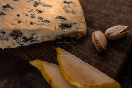 Photo for Close up view of cheese platter with dorblu, sliced pear and pistachios - Royalty Free Image