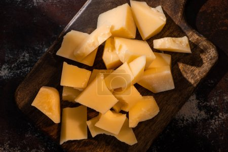 Photo for Top view of wooden platter with Grana Padano cheese on weathered surface in sunlight - Royalty Free Image