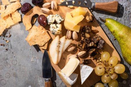 Photo pour Vue de dessus de différents types de fromage aux olives séchées, pistaches, raisins, poires et craquelins sur planche à découper - image libre de droit