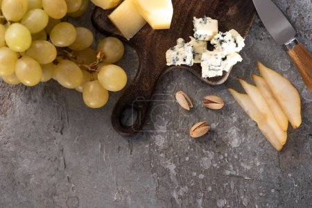 Photo for Top view of pieces of cheese on cutting board next to grapes, pistachios, knife and slices of pear on grey background - Royalty Free Image
