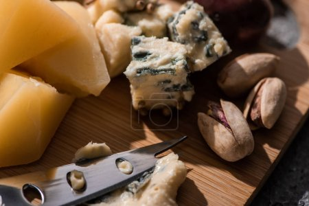 Selective focus of dorblu pressed by knife next to pieces of grana padano and pistachios on cutting board