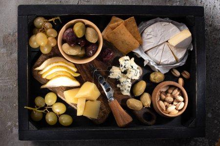 Photo pour Vue de dessus de différents types de fromage avec des fruits et des noix autour d'un couteau sur un plateau sur fond gris - image libre de droit