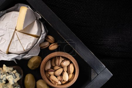 Photo for Top view of tray with pieces of camembert and dorblu, dried olives and pistachios isolated on black - Royalty Free Image