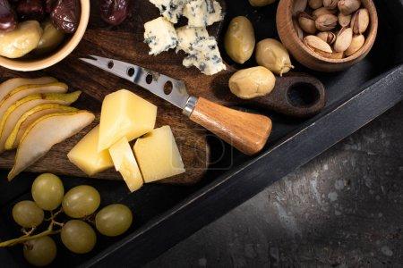 Foto de Vista superior de bandeja con piezas de queso, aceitunas secas, pistachos, lonchas de pera, uva y cuchillo en fondo gris. - Imagen libre de derechos