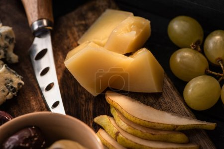 Photo for Selective focus of grana padano with pieces of pear, bowl of olives, knife, dorblu, grapes on cutting board - Royalty Free Image