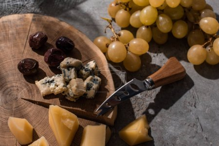 Photo for Grana padano and dorblu with olives and knife on round wooden board next to grapes on grey background - Royalty Free Image