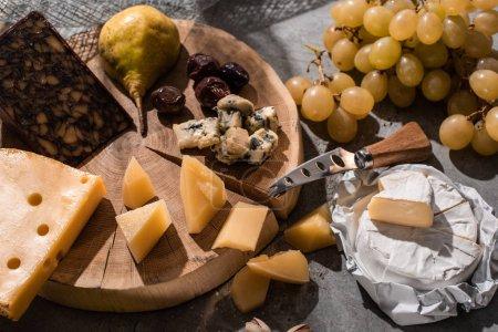 Photo pour Différents types de fromage avec des fruits, des olives et un couteau sur une planche de bois sur fond gris - image libre de droit
