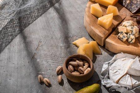 Photo pour Vue en grand angle de la poire, des pistaches et du camembert à côté de différents types de fromage sur planche de bois sur fond gris - image libre de droit