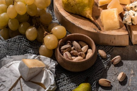 Photo for Cheese with pear on wooden board next to grapes, pistachios and Camembert on grey background - Royalty Free Image