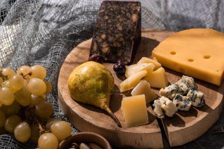 Photo pour Concentration sélective de différents types de fromage avec poire et olives sur planche de bois à côté de raisins et pistaches sur fond gris - image libre de droit