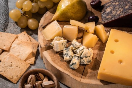 Photo pour Concentration sélective de différents types de fromage avec poire et olives sur une planche de bois à côté de raisins, noix et craquelins - image libre de droit