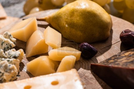 Photo for Selective focus of different kinds of cheese with dried olives and pear on round wooden board - Royalty Free Image